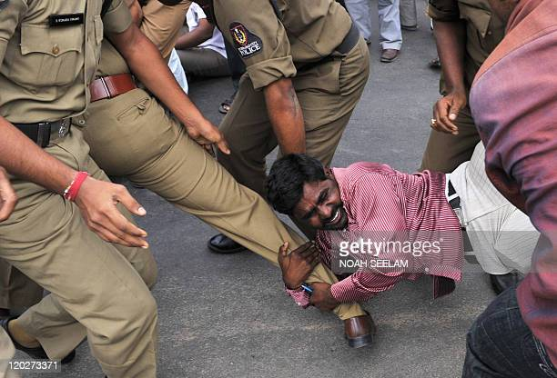 A demonstrator reacts while being arrested by police during a protest organised by members of the Communist Party of India and Communist Party of...