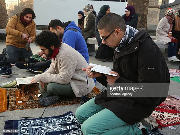A demonstrator reads holy Quran as they gather at Breitscheidplatz square to protest against the Chapel Hill shooting in Berlin Germany on February...
