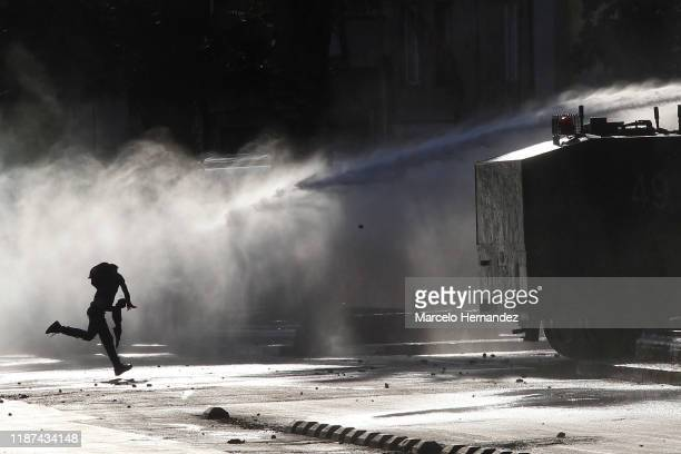 Demonstrator receives a shot of water by a watter cannon during the protest against government of President Sebastian Piñera on December 09, 2019 in...