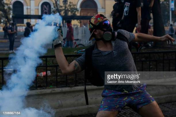 A demonstrator returns a gas canister to riot police officers during protests against the government of Sebastián Piñera on its second anniversary on...