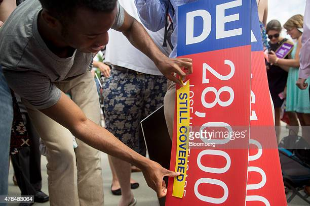 Demonstrator Ron Busby with Center for American Progress places a Still Covered sticker on a sign showing the number of people that would lose health...