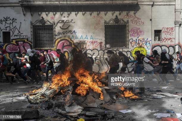 Demonstrator run past burning debris at Plaza Italia during the fifth straight day of protest which erupted over a now suspended hike in metro ticket...