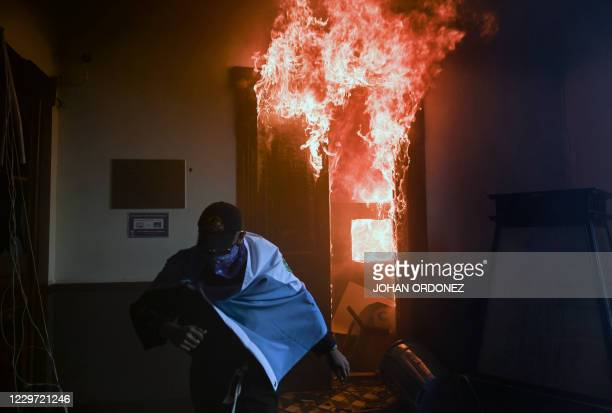 Demonstrator runs after setting on fire an office of the Congress building during a protest demanding the resignation of Guatemalan President...