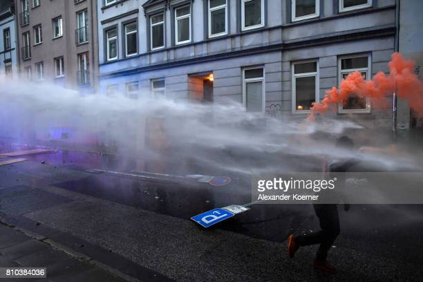 Demonstrator runs as police use water cannons during an anti-G20 protest on July 7, 2017 in Hamburg, Germany. Authorities are braced for large-scale...