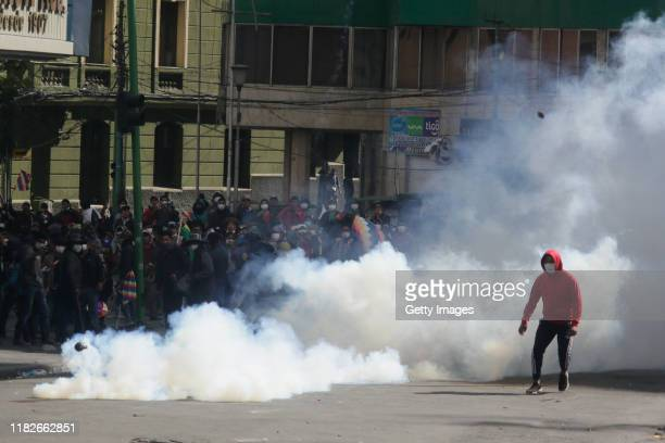 A demonstrator runs away from a cloud of tear gas during a protest on November 15 2019 in La Paz Bolivia Morales flew to Mexico alleging a coup under...