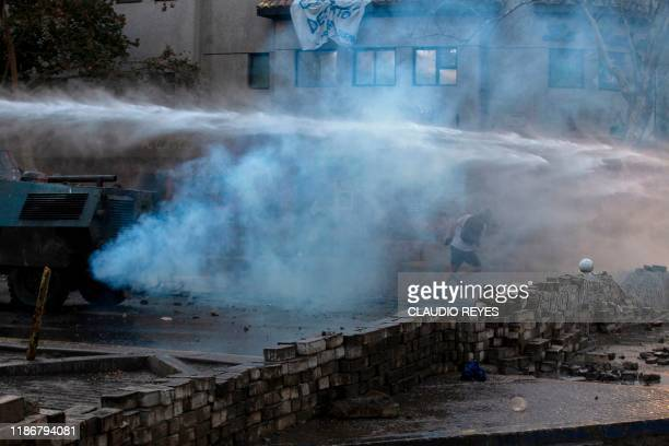 A demonstrator runs away from a spray of a riot police water cannon during a protest against the government in Santiago on December 06 2019 Thusands...