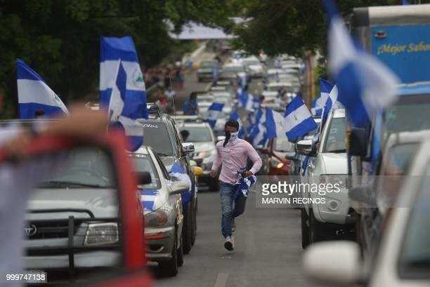 A demonstrator runs between two lines of cars during the march in cars and motorcycles from Managua to Ticuantepe 15km south of Managua demanding the...