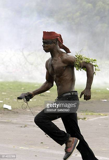 A demonstrator runs in front of smoke coming from tear gas launched by French gendarmes 05 October 2004 during a protest at the French military...