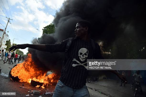 TOPSHOT A demonstrator runs next burning tires during a march in PortauPrince on January 23 to protest against the presidential elections and to...