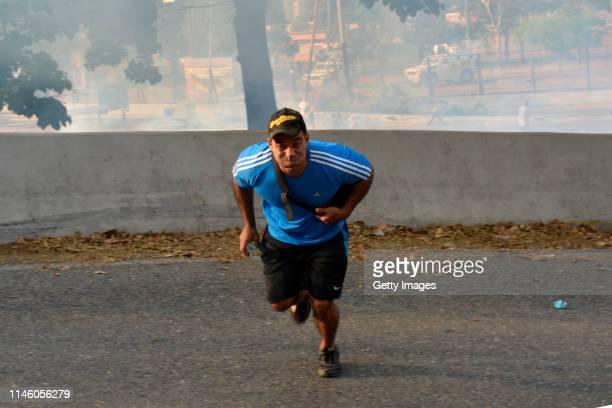 A demonstrator runs outside air force base La Carlota on April 30 2019 in Caracas Venezuela Through a live broadcast via social media Venezuelan...