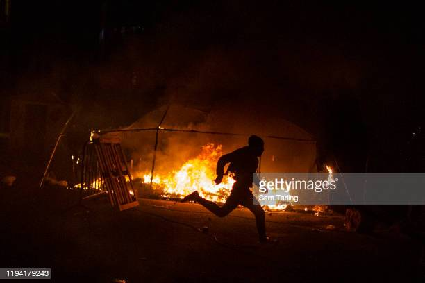 Demonstrator runs past a burning tent after riot police used tear gas and water cannon to disperse anti-government protesters as they clashed for the...