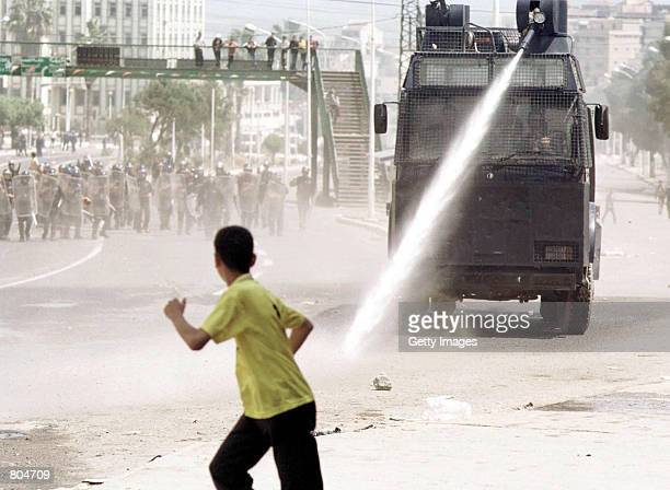 A demonstrator runs to avoid water cannon during riots April 26 2001 in the Berber capital of Tizi Ouzou Algeria 62 miles east of Algiers Rioting...
