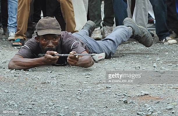 A demonstrator sarcastically aims a golf club as protesting residents face riot police while marching on the main road leading into the town of...