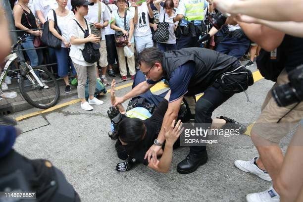 A demonstrator seen clashing with a police officer during the march Hundreds of thousands of demonstrators took to the street of Hong Kong to protest...
