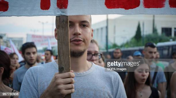 A demonstrator seen holding a banner during the antiwar protest on the occasion of the NATO summit in Brussels