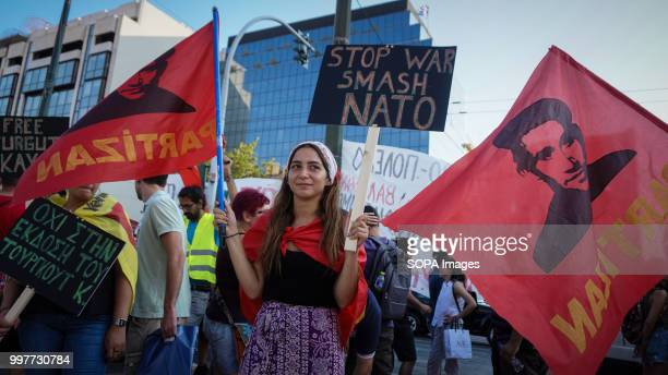 A demonstrator seen holding placards and flags during the antiwar protest on the occasion of the NATO summit in Brussels