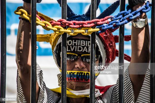 A demonstrator seen protesting behind bars during a protest The NGO Foro Penal carried out a street activity for the release of political prisoners...