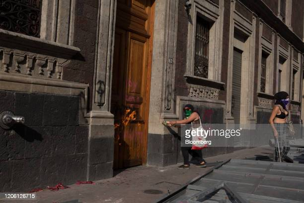 A demonstrator sets an entrance of a building on fire during a rally on International Women's Day in Mexico City Mexico on Friday March 8 2020 The...
