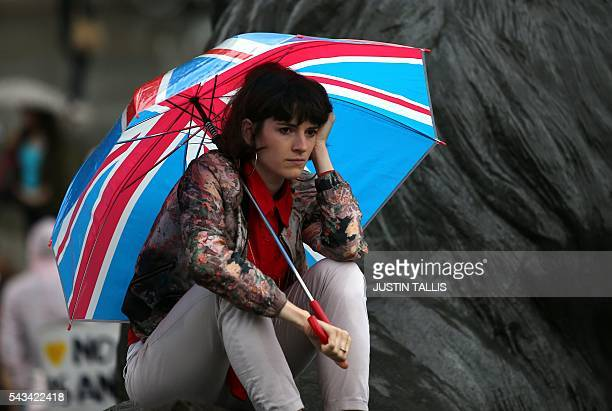 A demonstrator shelters under a Union flag umbrella people gather for an antiBrexit protest in Trafalgar Square in central London on June 28 2016 EU...