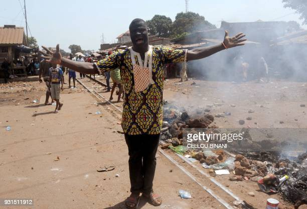 TOPSHOT A demonstrator shouts as he stands beside a burning barricade on a street in Conakry on March 13 which was erected by demonstrators during a...