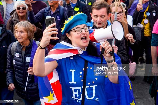 A demonstrator shouts into a megaphone as she marches with others holding placards and EU and Union flags during a rally by the People's Vote...