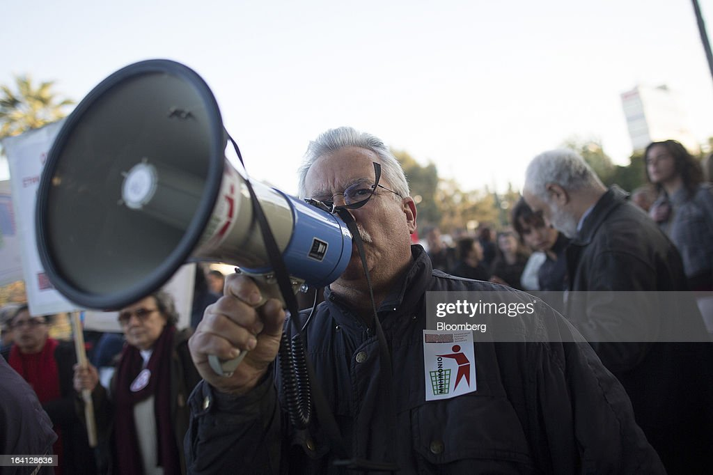 A demonstrator shouts through a megaphone during a protest outside the parliament against bank deposit tax plans in Nicosia, Cyprus, on Tuesday, March 19, 2013. Euro-area finance ministers told Cyprus to raise 5.8 billion euros ($7.5 billion) from bank depositors to unlock emergency loans, maintaining the revenue target while suggesting sparing small-scale savers. Photographer: Simon Dawson/Bloomberg via Getty Images