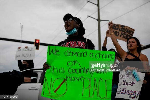 Demonstrator shouts while holding a sign during a protest against police brutality and the recent death of George Floyd in Sunrise, Florida on June...