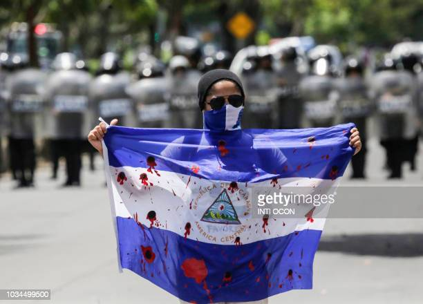 TOPSHOT A demonstrator shows a bloody flag during a protest against Nicaraguan President Daniel Ortega's government in Managua on September 16 2018