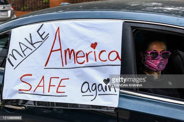 """Demonstrator shows a sign with """"Make America safe again"""" written on it while driving past the Governor's Mansion during a drive by protest in..."""