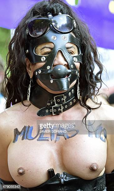 A demonstrator shows her breasts covered with the slogan 'fines no' as she covers her face with a bondage style mask during a demonstration against...