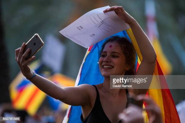 A demonstrator shows takes a selfie holding an official ballot as she demonstrate in front of the Catalan High Court building on September 21 2017 in...