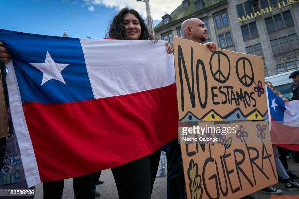 A demonstrator shows the Chilean flag next to a placard that says we are not at war during the demonstration organized today in Amsterdam in support...