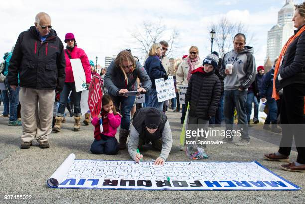 A demonstrator signs a banner during the March For Our Lives Rally on March 24 at the Connecticut State Capitol in Hartford CT