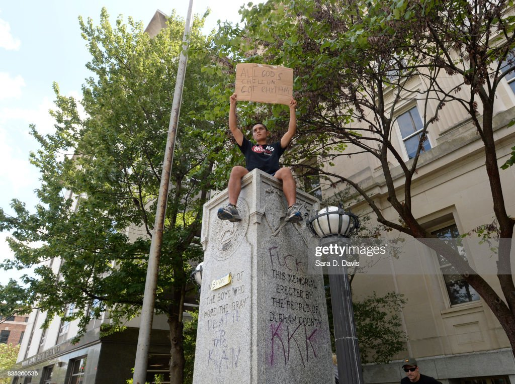 A demonstrator sits atop the defaced pedestal of where a Confederate soldier statue once stood during a rally on August 18, 2017 in Durham, North Carolina. Demonstrations come a week after a fatal clash during a 'Unite the Right' rally between white supremacists and counter protesters in Charlottesville, Virginia.