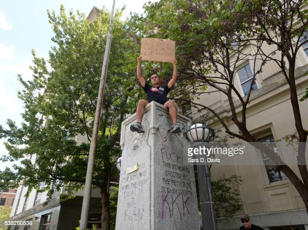 A demonstrator sits atop the defaced pedestal of where a Confederate soldier statue once stood during a rally on August 18 2017 in Durham North...