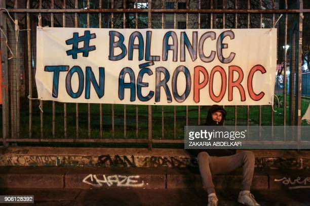 A demonstrator sits by a hashtag banner reading 'Balance ton Aeroporc' playing on words between airport and pig refering to the #MeToo and...