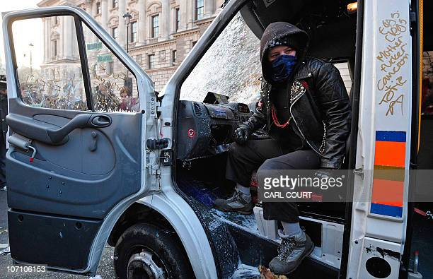 A demonstrator sits in a vandalised Police van during a protest over tuition fees on Whitehall in central London on November 24 2010 A student mob...