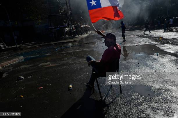 A demonstrator sits on a chair in the street waving a Chilean flag during the seventh day of protests against President Sebastian Piñera on October...