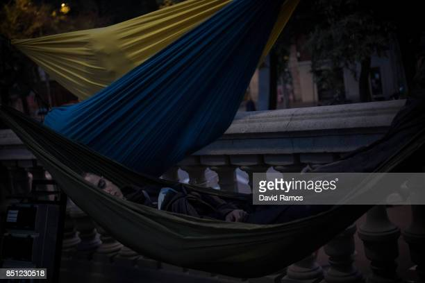 A demonstrator sleeps on a hammock after spending the night in front of the Catalan High Court building on September 22 2017 in Barcelona Spain...