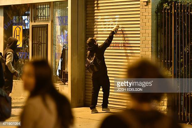 A demonstrator spray paints a wall during a May Day protest in Oakland California on May 1 2015 Hundreds marched throughout the city vandalizing...