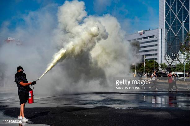 Demonstrator sprays a fire extinguisher during clashes with riot police following a protest against Chilean President Sebastian Pinera's government...