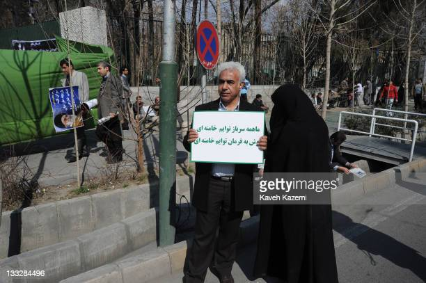 Demonstrator standing in front of Tehran University with his chador-clad wife, holds a banner pledging obedience to Ayatollah Ali Khamenei, the...