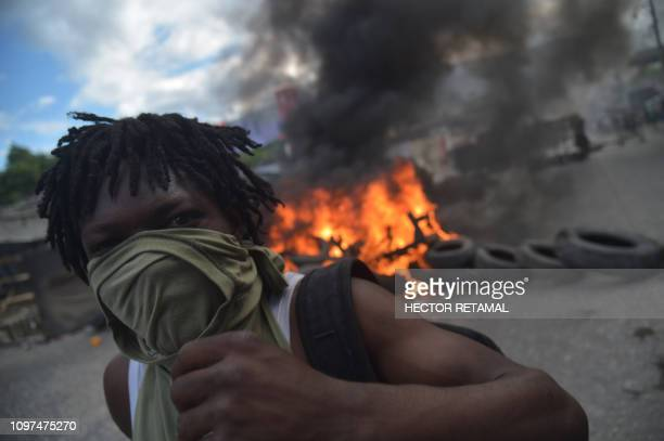 Demonstrator stands before a barricade of burning tires on the fourth day of protests in Port-au-Prince, on February 10, 2019. - Demonstrators are...