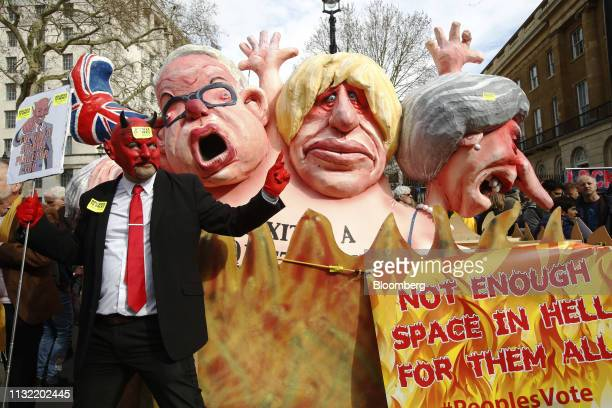 A demonstrator stands by a sculpture depicting Michael Gove UK environment secretary Boris Johnson former UK foreign secretary and Theresa May UK...