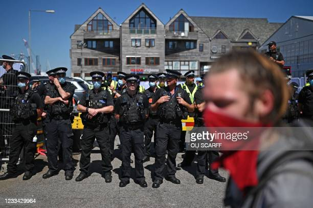 Demonstrator stands in front of a line of police at a protest against the Police, Crime, Sentencing and Courts Bill 2021 in Falmouth, Cornwall on...