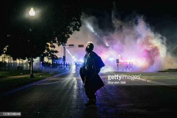 Demonstrator stands in the street with a make-shift shield on August 25, 2020 in Kenosha, Wisconsin. As the city declared a state of emergency...