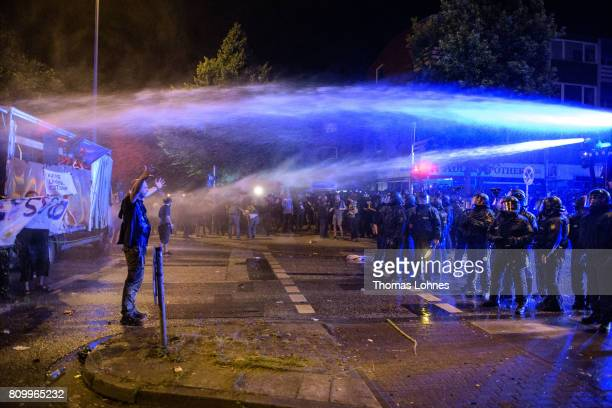 A demonstrator stands in the water jet from police water cannon in front of the Rote Flora leftwing centre after the 'Welcome to Hell' protest march...