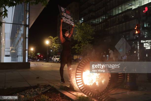 A demonstrator stands near a trash can fire near the White House while protesting the killing of George Floyd in the early morning hours on May 31...