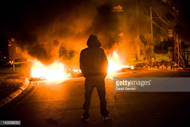 A demonstrator stands next to a barricade of burning tires at the main entrance of Mercabarna the biggest wholesale market of Barcelona on March 29...