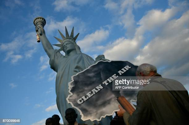 A demonstrator stands next to a mockup of the Statue of Liberty as he takes part in a socalled Climate March against fossilbased energy like coal on...